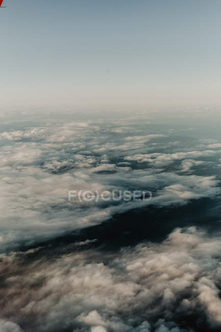 From above of white clouds in sky over dark landscape — Stock Photo