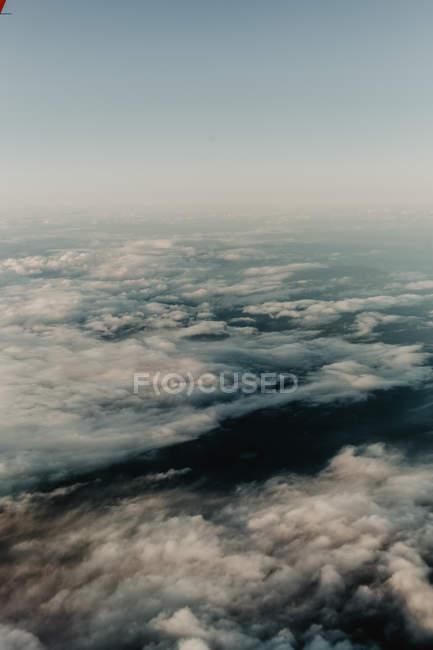 Dall'alto di nuvole bianche in cielo sopra paesaggio scuro — Foto stock