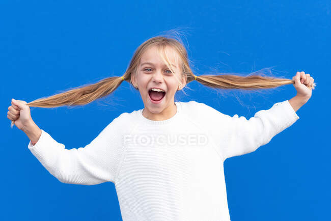 Overjoyed girl holding pigtails and laughing — Stock Photo