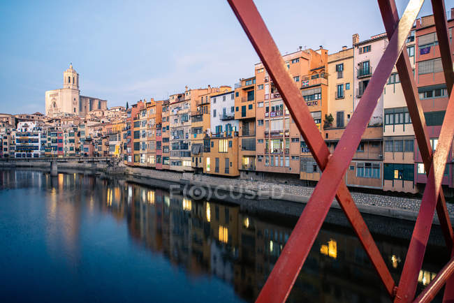 Paysage pittoresque de la ville des immeubles d'appartements situés sur le canal derrière la rampe de pont rouge en début de soirée, Gérone, Espagne — Photo de stock