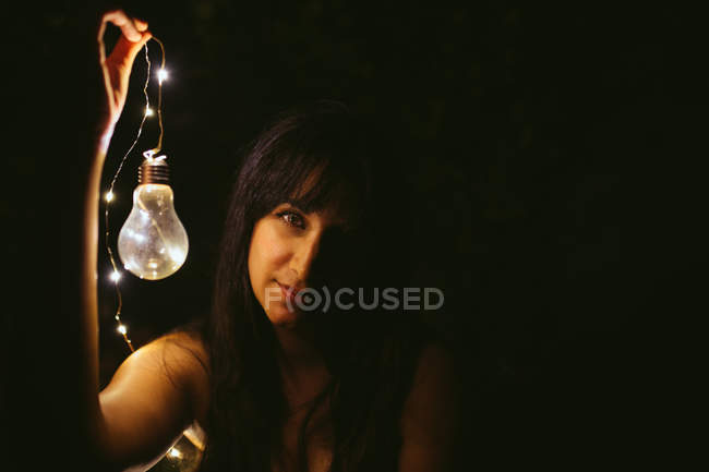 Thoughtful young woman holding decorative burning light bulb in darkness — Stock Photo