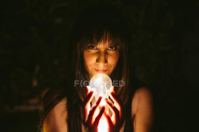 Giovane donna che tiene bulbo ardente nelle mani nell'oscurità — Foto stock