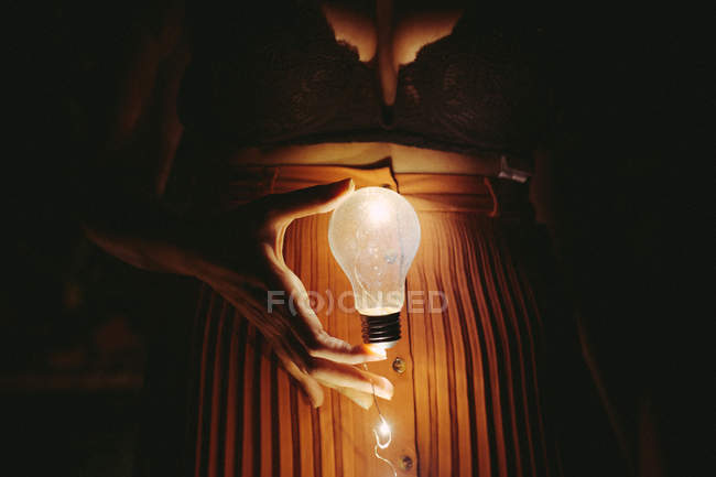 Midsection of woman holding bright lightbulb in darkness — Stock Photo