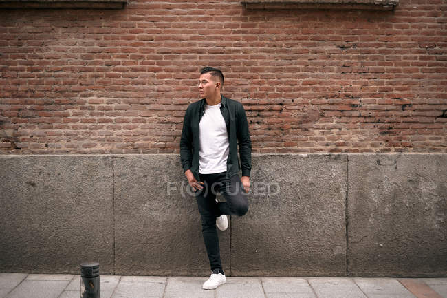 Confident young man at brick wall in street — Stock Photo