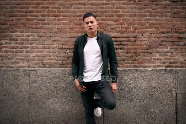 Serious youthful male in casual clothes looking at camera and standing at red brick wall in street — Stock Photo