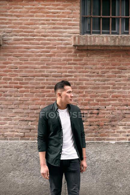 Уверенный молодой человек у кирпичной стены на улице — стоковое фото