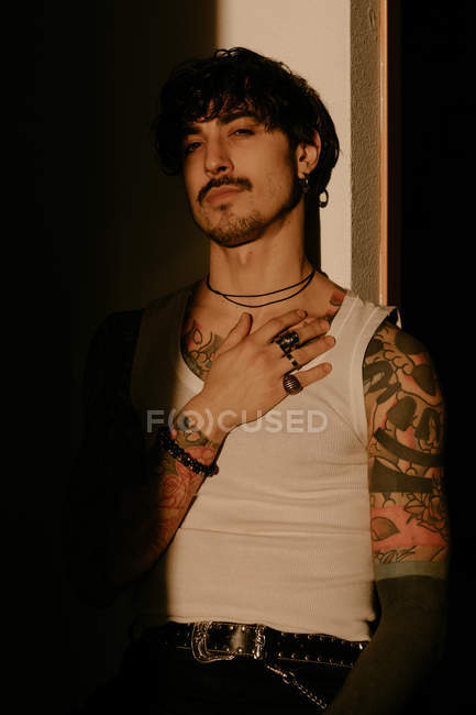 Young stylish guy with mustache and tattoos in white tank top leaning against wall, looking in camera — Stock Photo