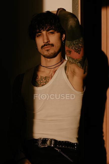 Young stylish hipster man with tattoos in white tank top leaning against wall, looking in camera — Stock Photo