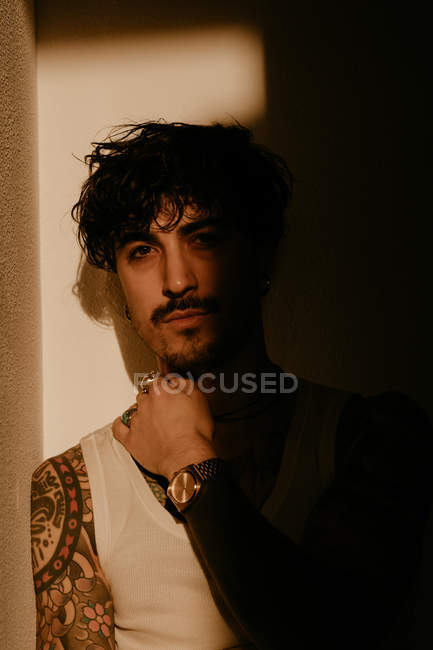 Young handsome man with mustache and tattoos leaning against wall in shadow — Stock Photo