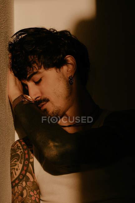 Giovane bell'uomo con baffi e tatuaggi appoggiato al muro in ombra — Foto stock