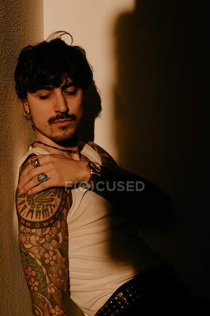 Joven hombre guapo con mustache y tatuajes inclinándose contra la pared en la sombra. - foto de stock