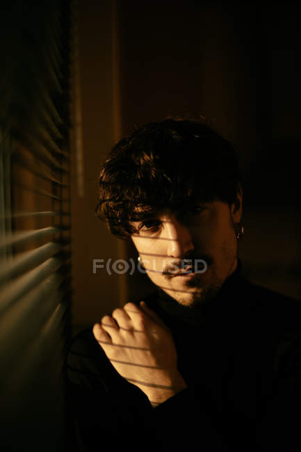 Young melancholic guy in black turtleneck standing next to window with shutters with shadow on face looking in camera — Stock Photo