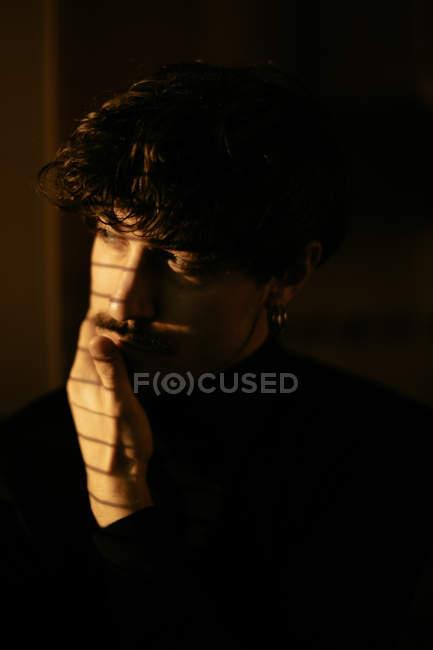 Junger melancholischer Typ in schwarzem Rollkragen, der neben dem Fenster steht, mit Rollläden mit Schatten auf dem Gesicht, der wegschaut — Stockfoto