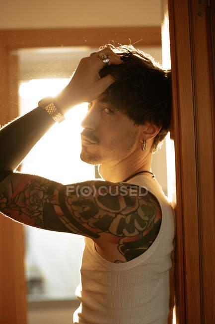 Vista laterale di giovane ragazzo alla moda con baffi e tatuaggi appoggiati al muro — Foto stock