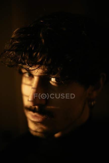 Bello malinconico ragazzo in nero dolcevita in piedi accanto alla finestra con persiane, guardando in macchina fotografica — Foto stock