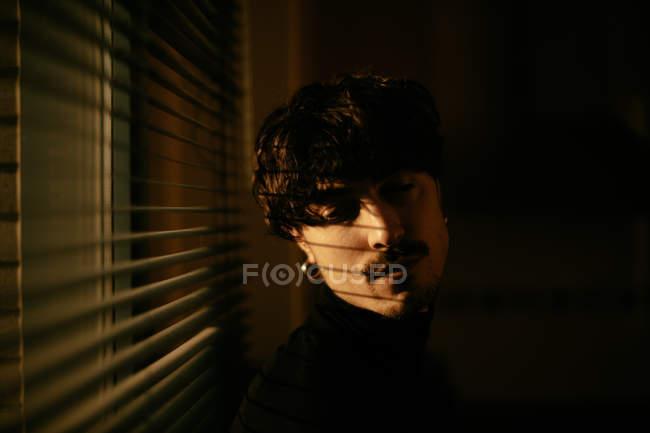 Schöner melancholischer Typ in schwarzem Rollkragen, der neben einem Fenster mit Rollläden steht und nach unten schaut — Stockfoto