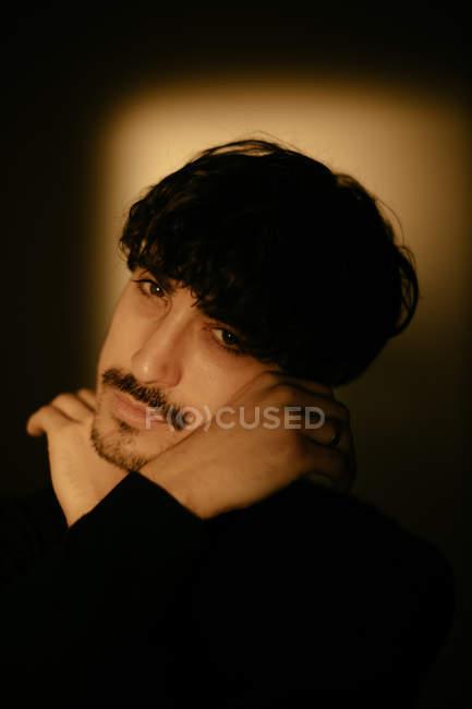Joven con mustache junto a la pared mirando en la cámara. - foto de stock