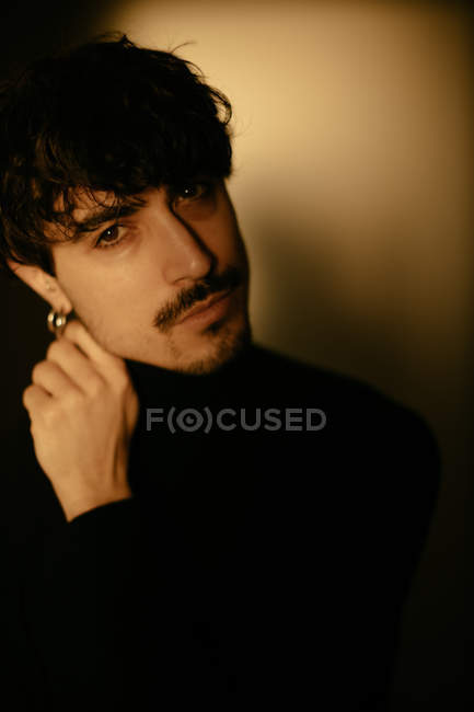 Young man with mustache next to wall looking in camera with hand on chin — Stock Photo