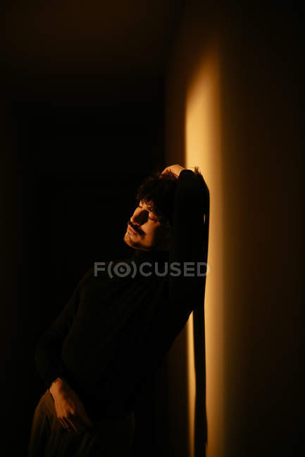 Pensive man with mustache sitting next to wall with raised arm — Stock Photo