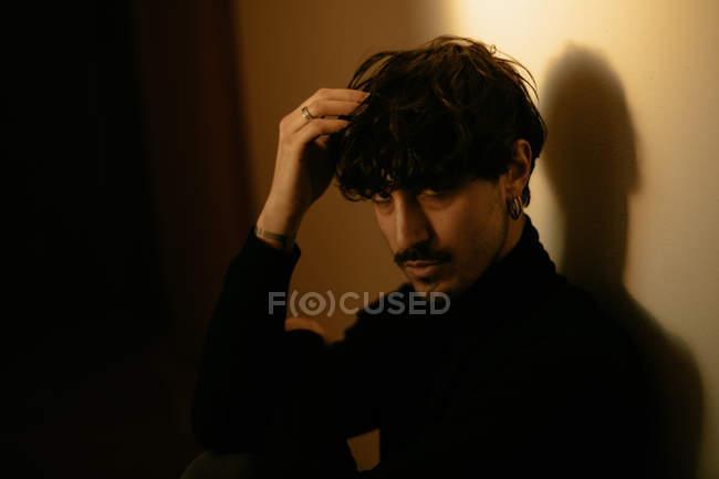 Giovane uomo alla moda con i baffi seduto accanto al muro con braccio alzato sopra la testa — Foto stock