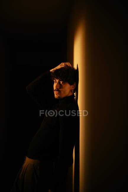 Junger trendiger Mann mit Schnurrbart sitzt mit erhobenem Arm über dem Kopf an der Wand — Stockfoto