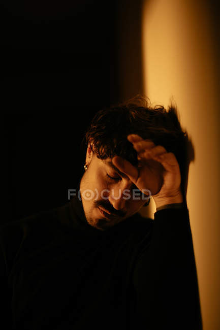 Young man with mustache sitting next to wall with closed eyes — Stock Photo