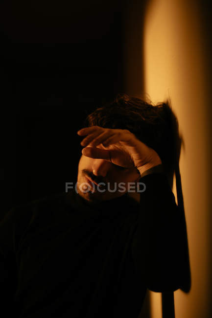Young man with mustache next to wall with closed eyes — Stock Photo