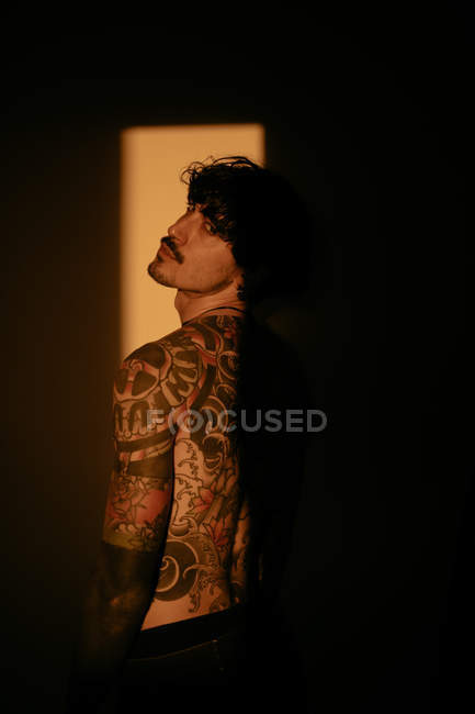 Handsome shirtless tattooed man posing sensually in sunlight — Stock Photo