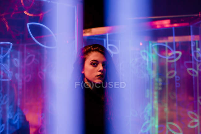 Young long-haired woman in trendy wear looking in camera among neon signs at city street — Stock Photo