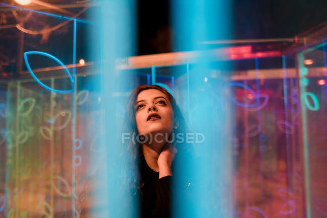 Young woman with stylish makeup looking up as standing among neon signs at city street — Stock Photo