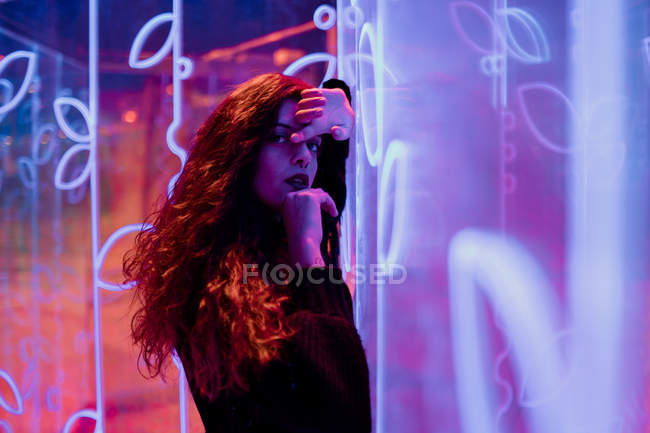 Stylish melancholic brunette in lights of neon signs leaning on wall at city street — Stock Photo