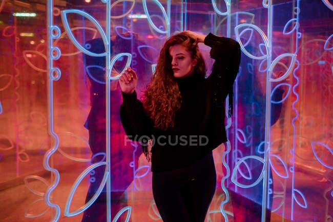 Mujer joven bastante pensativa con los ojos cerrados entre los letreros de neón en la calle de la ciudad - foto de stock