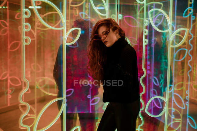 Beautiful melancholic brunette with long hair standing among neon signs at city street — Stock Photo