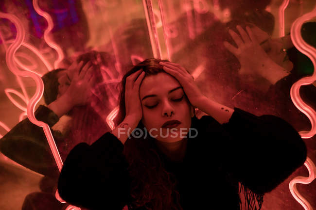 Stylish melancholic woman with closed eyes and head in hands at city street — Stock Photo