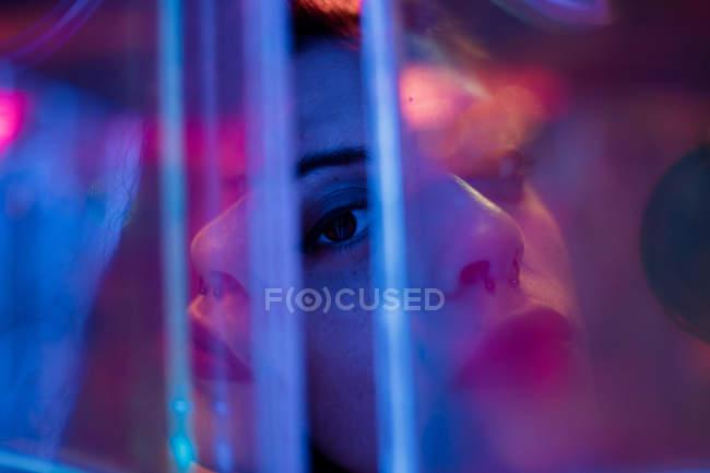 Жінка зблизька дивиться в камеру серед барвистих неонових вогнів на вулиці міста — стокове фото