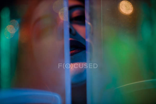 Close-up of woman with closed eyes among colorful neon lights at city street — Stock Photo