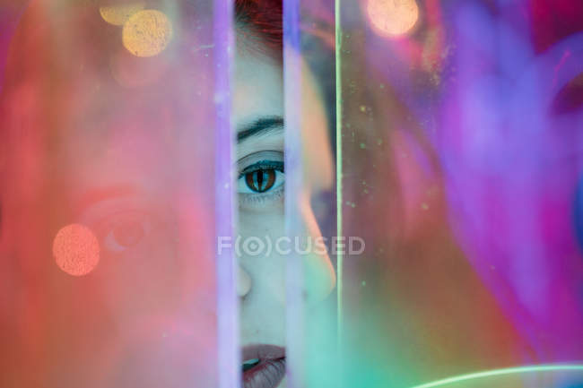 Close-up of woman looking in camera among colorful neon lights at city street — Stock Photo
