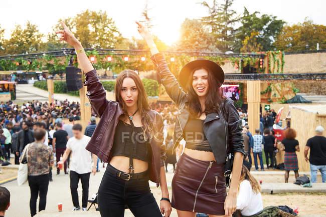 Друзі з довгим волоссям в шкіряній куртці і капелюсі, танцюють піднімаючи руки двома пальцями вгору і дивляться на камеру в сонячний день. — стокове фото
