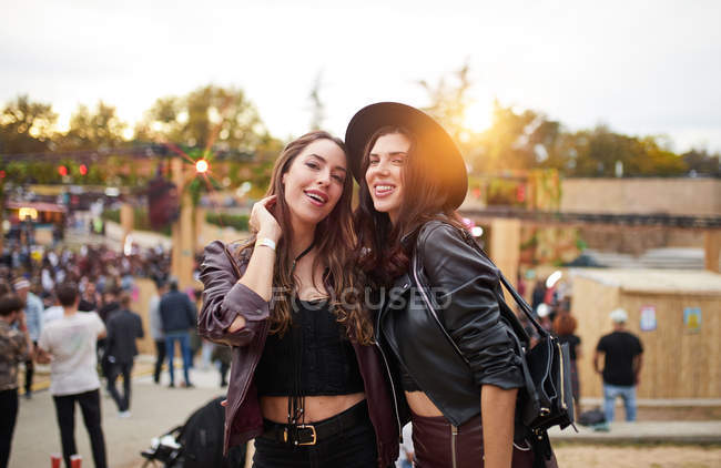 Long haired fashion friends in leather jacket and hat dancing raising hands with two fingers up and looking at camera on festival in sunny day — Stock Photo
