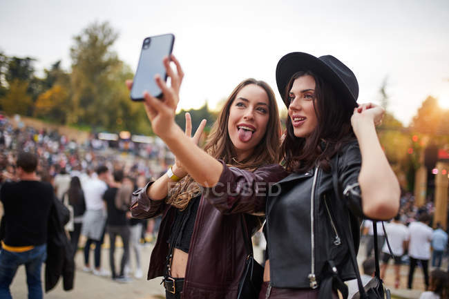 Charming cheerful friends in black hat having fun grimacing and taking selfie on mobile phone in bright day at festival — Stock Photo