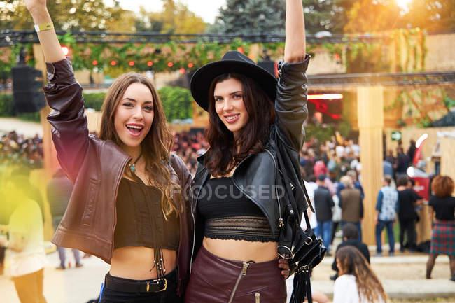Amigos de la moda de pelo largo en chaqueta de cuero y sombrero bailando levantando las manos con dos dedos hacia arriba y mirando a la cámara en el festival en un día soleado - foto de stock