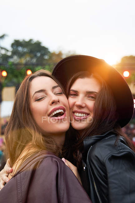 Charming long haired stylish girl friends confidently looking at camera in bright day at festival — Stock Photo
