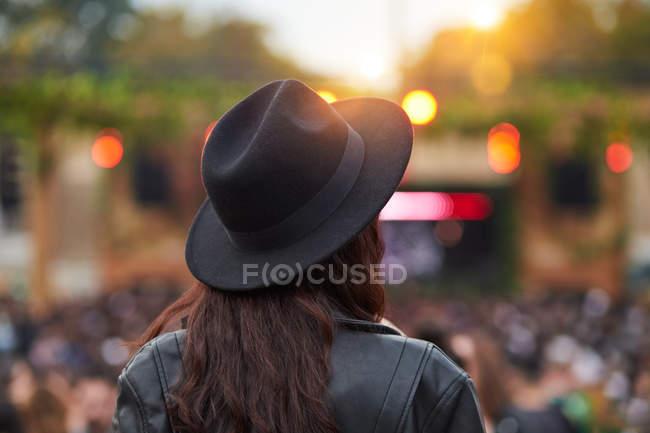 Погляд на жінку з довгим волоссям у чорному капелюсі та шкіряній куртці, яка насолоджується розвагами в парку під час свята в сонячний день. — стокове фото