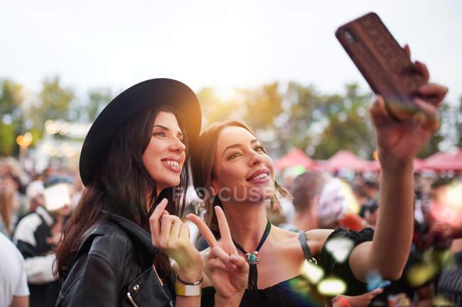 Charmant amis gais en chapeau noir s'amuser grimaçant et prendre selfie sur téléphone mobile dans la journée lumineuse au festival — Photo de stock