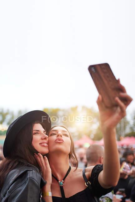 Amigos alegres encantadores em chapéu preto se divertindo sorrindo e tirando selfie no telefone celular em dia brilhante no festival — Fotografia de Stock