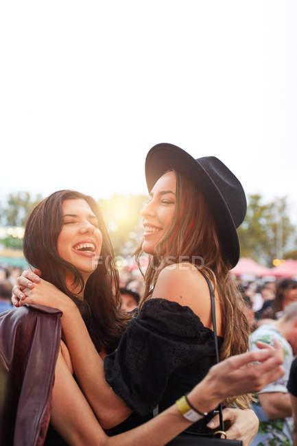 Charmante longue chevelure amis élégants s'amuser dans la journée lumineuse au festival — Photo de stock