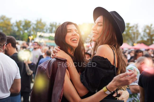Encantador de cabelos longos amigos elegantes se divertindo no dia brilhante no festival — Fotografia de Stock