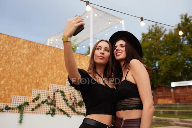 Стильные веселые друзья в черной шляпе обнимаются и делают селфи на мобильном телефоне в яркий день на украшенной арене на фестивале — стоковое фото