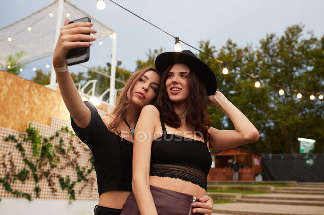 Stylish cheerful friends in black hat embracing and taking selfie on mobile phone in bright day at decorated arena on festival — Stock Photo