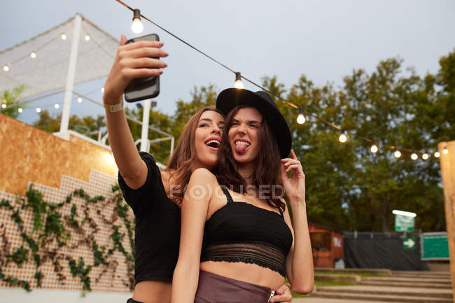 Friends in black hat embracing and taking selfie on mobile phone in bright day at decorated arena on festival — Stock Photo